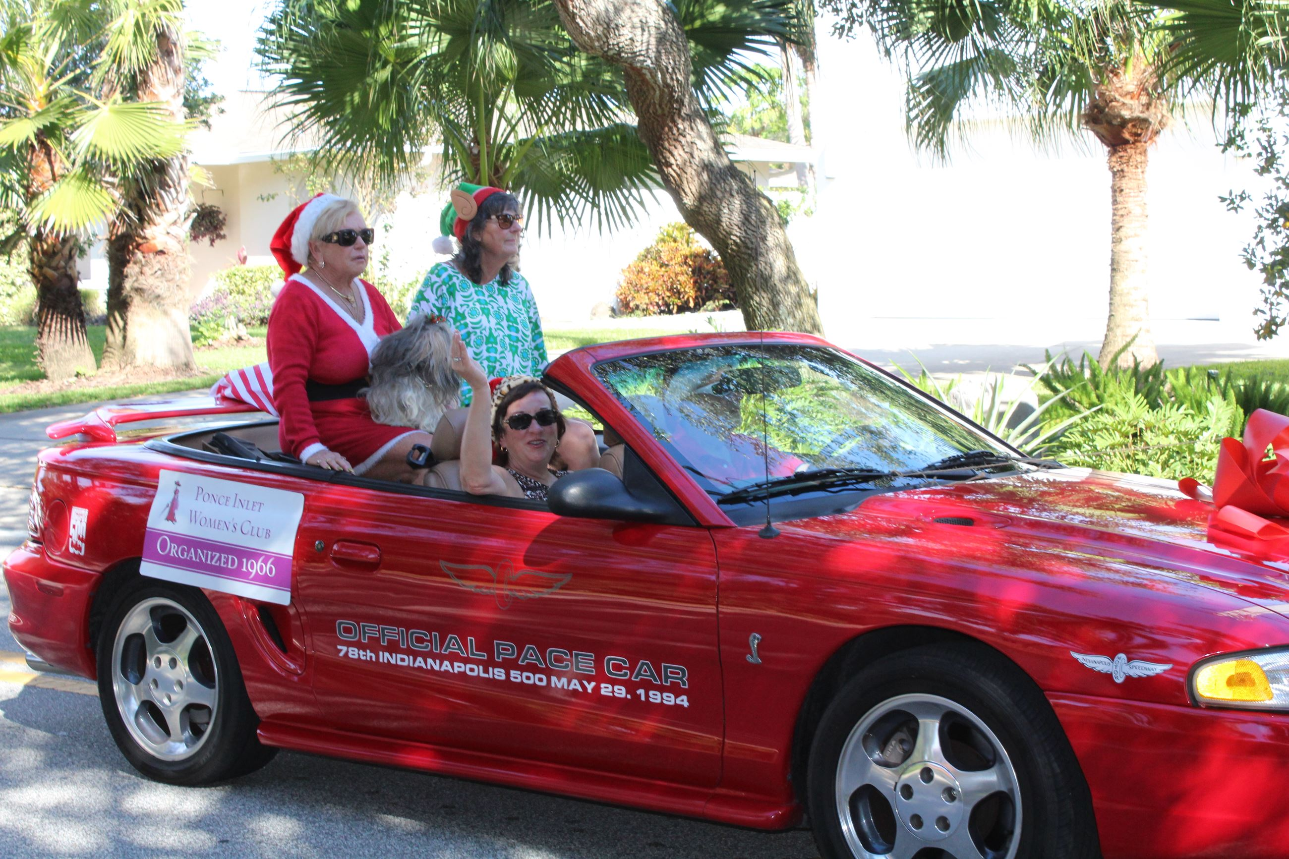 three woman riding in red convertible with top down