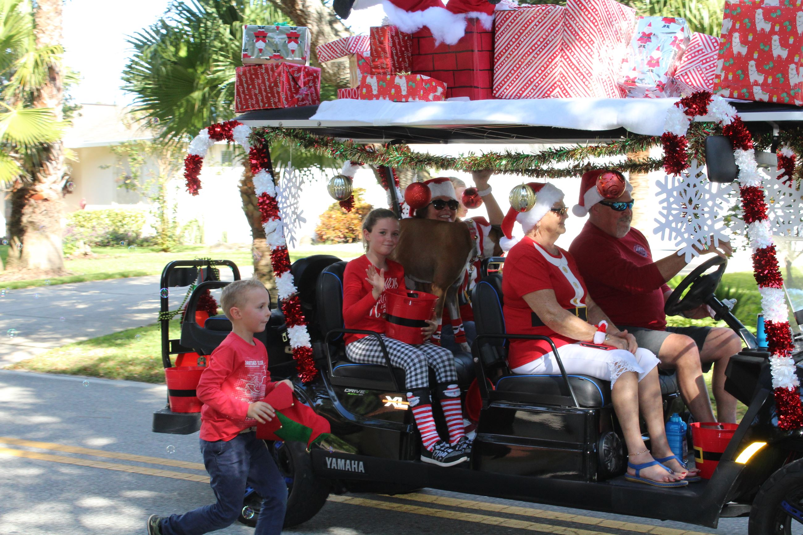 family riding in holiday decorated golf cart