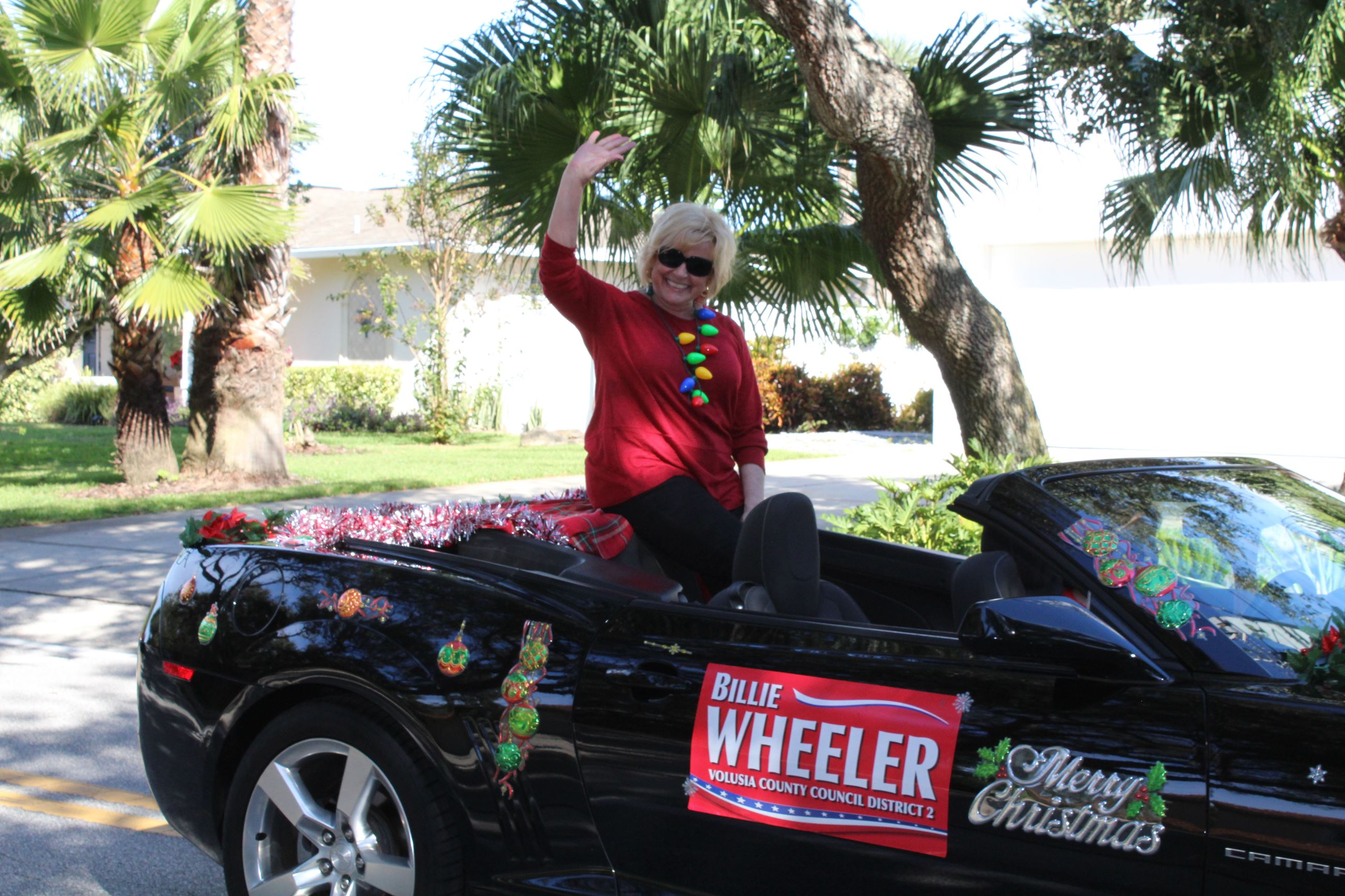 Billie Wheeler riding in red convertible waving
